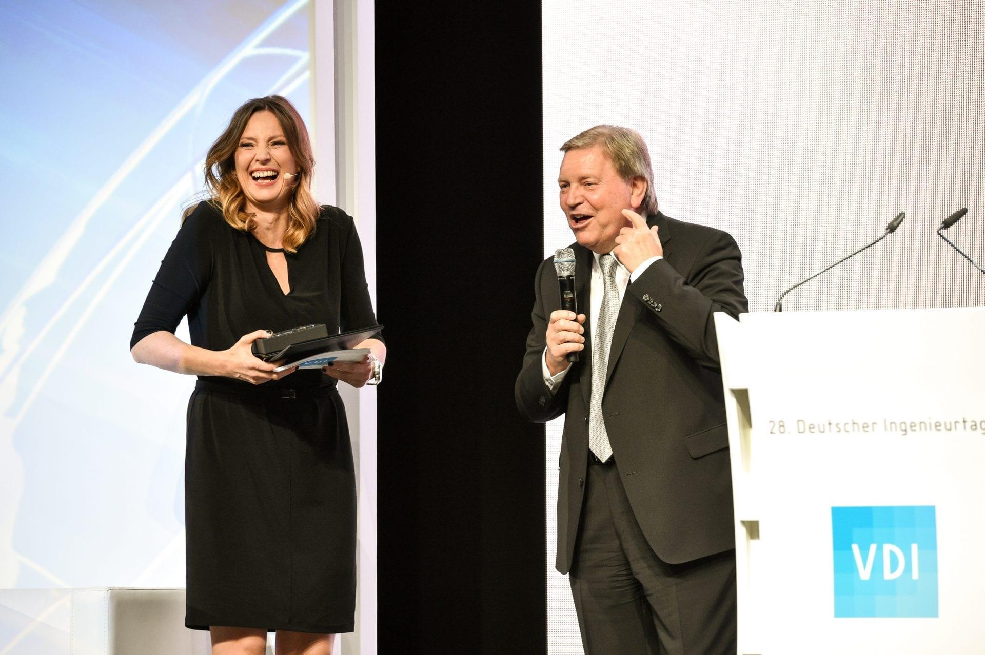 Gala-Moderatorin Kristina zur Mühlen lacht herzlich beim Bühnentalk mit Preisträger Rainer Hirscherberg