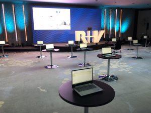 Geöffnetes Laptop auf kleinem runden Tisch im Saal mit vielen runden Tischen