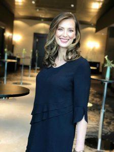 Moderatorin Kristina zur Mühlen lacht in Kamera |trägt dunkelblaues Kleid
