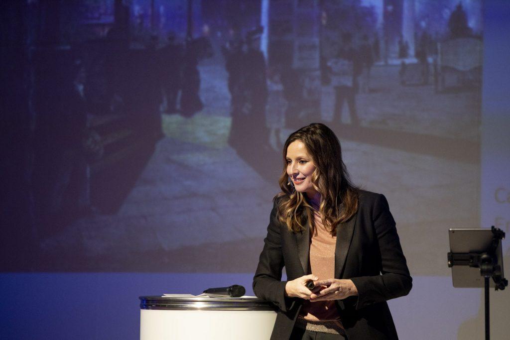 KeynoteSpeakerin Kristina zur Mühlen lächelt auf Bühne ins Publikum