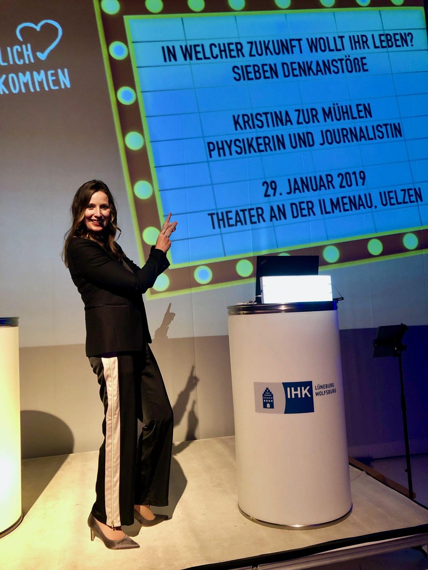 Kristina zur Mühlen auf Bühne |zeigt auf Leinwand mit Keynote-Titel