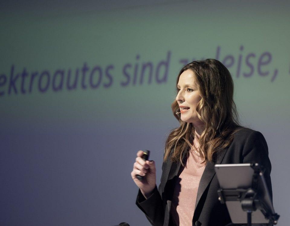 KeynoteSpeakerin Kristina zur Mühlen auf Bühne |mit Presenter in der Hand |Thema Elektroautos
