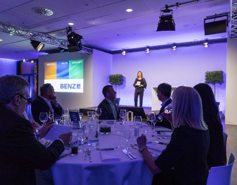 Kristina zur Mühlen auf Bühne | begrüßt Gäste | Gäste sitzen an runden Tischen