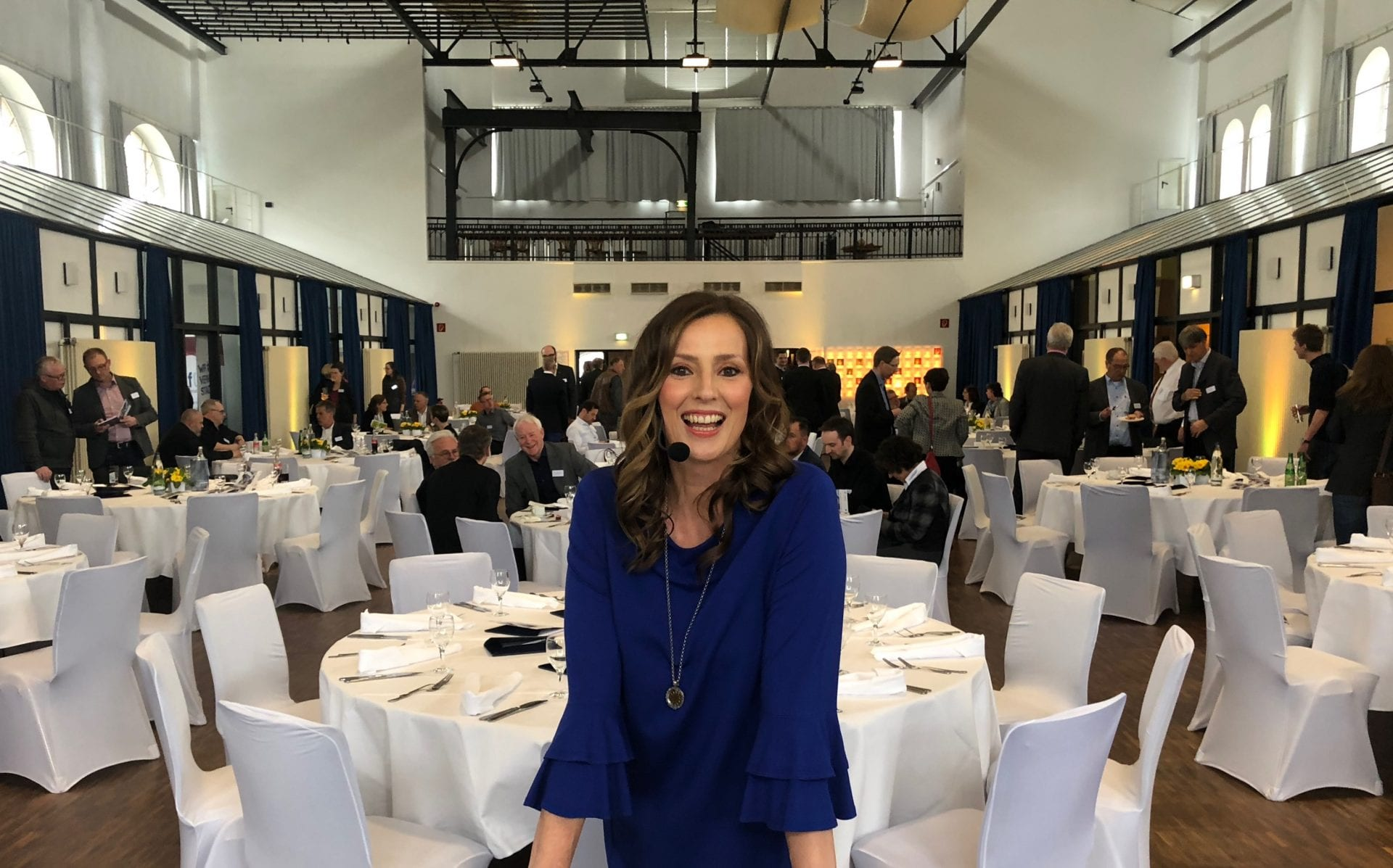 Kristina zur Mühlen im Saal vor gedeckten Tischen |blaues Kleid