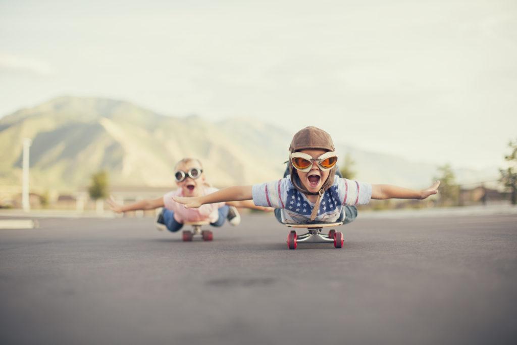 Kinder liegen auf ihren Skateboards