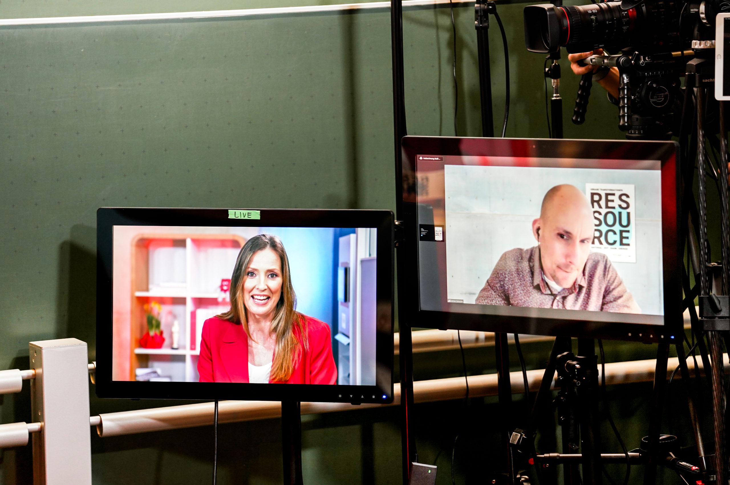zwei Monitore stehen nebeneinander mit Moderatorin und Speaker